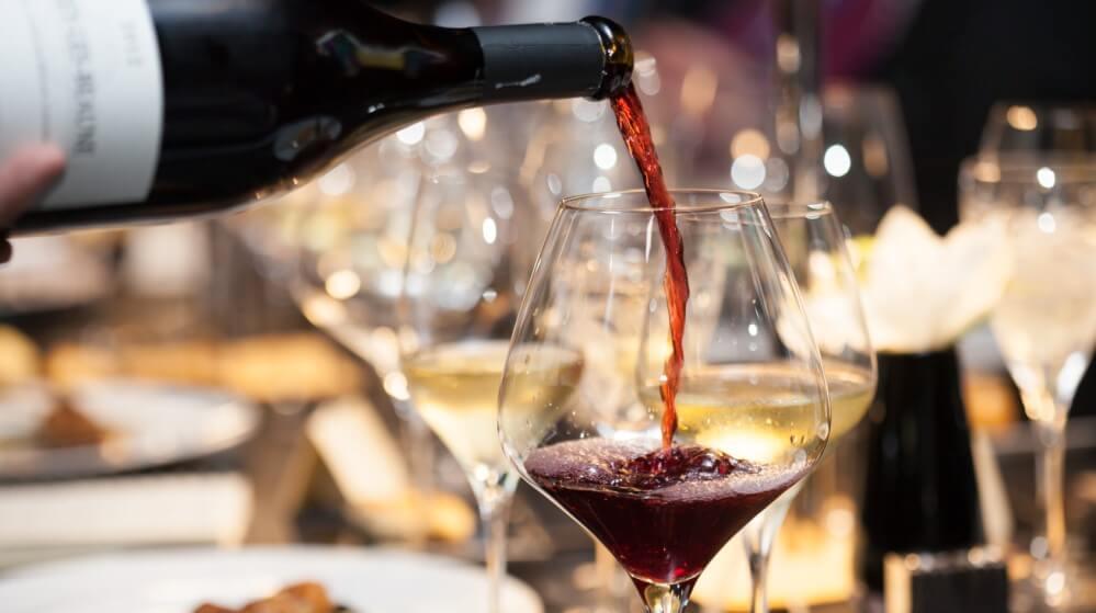Wein wird bei einem festlichen Tisch zu Ostern passend zum Osteressen eingeschenkt